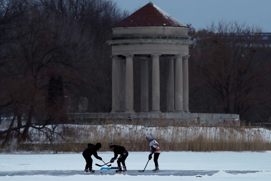 Youths play ice hockey on a frozen pond at Franklin Delano Roosevelt Park in Philadelphia during Thursday's winter storm.