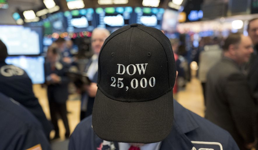 A stock trader wears a Dow 25,000 hat, Thursday, Jan. 4, 2018, at the New York Stock Exchange. The Dow Jones industrial average closed above 25,000 points for the first time, just five weeks after its first close above 24,000. (AP Photo/Mark Lennihan)