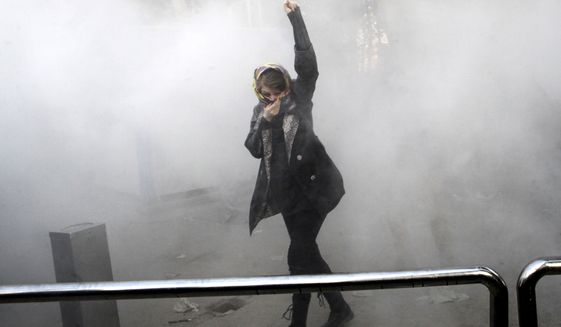 In this Saturday, Dec. 30, 2017, photo, taken by an individual not employed by the Associated Press and obtained by the AP outside Iran, a university student attends a protest inside Tehran University while a smoke grenade is thrown by anti-riot Iranian police, in Tehran, Iran. Iran's top regional foes, Israel and Saudi Arabia, are both watching that country's protests for signs they could lead to change. Iran's supreme leader has accused enemies of stoking the unrest. (Associated Press)