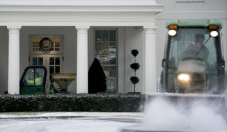 National Park Service workers clear snow on the North Lawn of the White House, Thursday, Jan. 4, 2018, in Washington. (AP Photo/Andrew Harnik)
