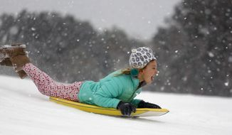 Finley Bork, 7, uses a boogie board, typically used on the beach, for sledding down a hill on a golf course at the Isle of Palms, S.C., Wednesday, Jan. 3, 2018.  A brutal winter storm smacked the coastal Southeast with a rare blast of snow and ice Wednesday, hitting parts of Florida, Georgia and South Carolina with their heaviest snowfall in nearly three decades. (AP Photo/Mic Smith)