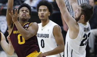 Arizona State guard Tra Holder, left, shoots as Colorado guard D'Shawn Schwartz, center, and forward Lucas Siewert defend during the first half of an NCAA college basketball game Thursday, Jan. 4, 2018, in Boulder, Colo. (AP Photo/David Zalubowski)