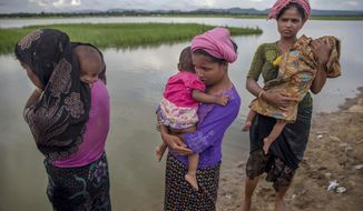 FILE- In this Oct. 18, 2017, file photo, Rohingya Muslim women, who crossed over from Myanmar into Bangladesh, stand holding their sick children after Bangladesh border guard soldiers refused to let them journey towards a hospital and turned them back towards the zero line border in Palong Khali, Bangladesh. An international aid agency projects that 48,000 babies will be born in overcrowded refugee camps this year for Rohingya who have fled to Bangladesh from neighboring Myanmar. Save the Children warned in a report released Friday, Jan. 5, 2018, that the newborns will be at an increased risk of disease and malnutrition, and therefore of dying before the age of five. (AP Photo/Dar Yasin, File)