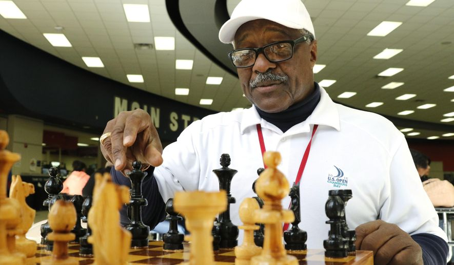 ADVANCED FOR USE MONDAY, JAN. 8 AND THEREAFTER Donald Harris, 66, a Duncanville school district bus driver plays chess with Duncanville High School student Pablo Ramirez (not pictured) during lunch in the school's cafeteria on Monday, Dec. 11, 2017 in Duncanville, Texas. Donald met a student on his bus route one day and asked if he wanted to learn to play chess. The student agreed and they became friends and played in a noisy cafeteria. Donald spends his lunch hour teaching the game of chess to students. (David Woo/The Dallas Morning News via AP)