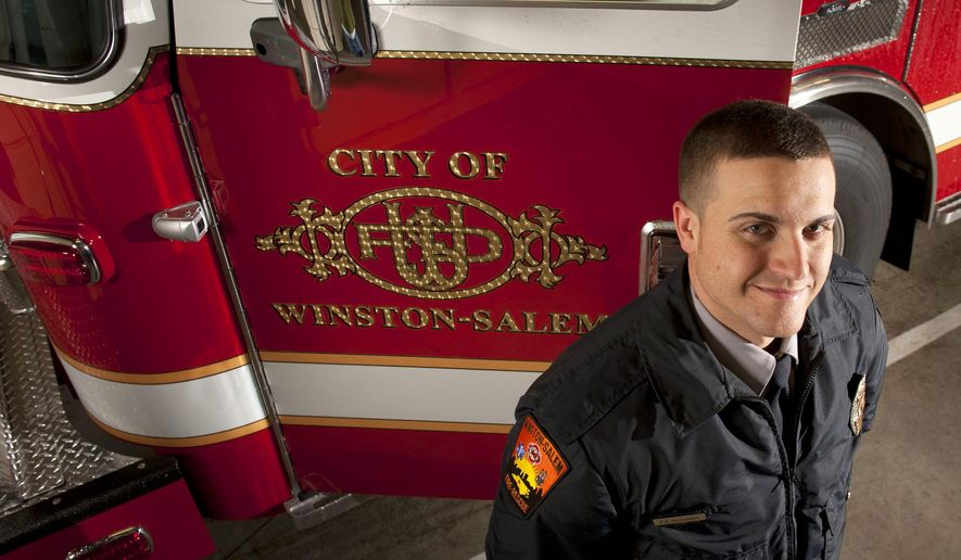 Firefighter Ethan Richards stands next to the new logo he designed for the Winston-Salem Fire Department, a scramble of the letters WSFD, in Winston-Salem, N.C. The new logo appears on all of the department's newest vehicles. (Walt Unks/Winston-Salem Journal via AP)