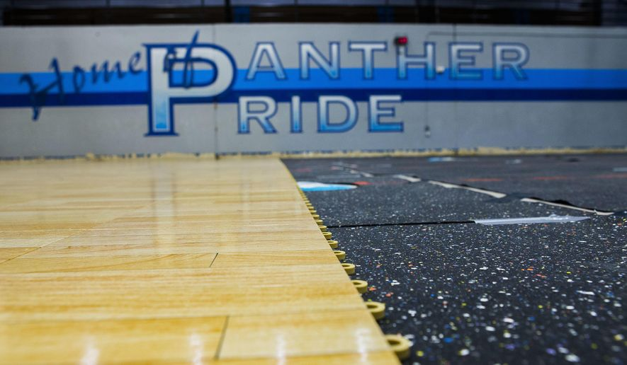 This photo taken Dec. 20, 2017, shows the new floor is being installed inside a gymnasium as staff prepare to move back in to C.E. King High School for the new semester starting in January after having to vacate the school due to damage from Hurricane Harvey in Houston. ( Mark Mulligan/Houston Chronicle via AP)