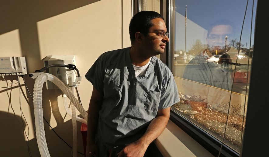 In this Dec. 20, 2017 photo, Quincy Medical Group's Sumul Gandhi poses for a photo in a  treatment room at QMG in Quincy, Ill. The 35-year-old dermatologist was valedictorian of his high school class, earned three masters degrees simultaneously and, in 2015, co-founded an online business that rents out healthcare spaces to physicians in need. (Jake Shane/The Quincy Herald-Whig via AP)
