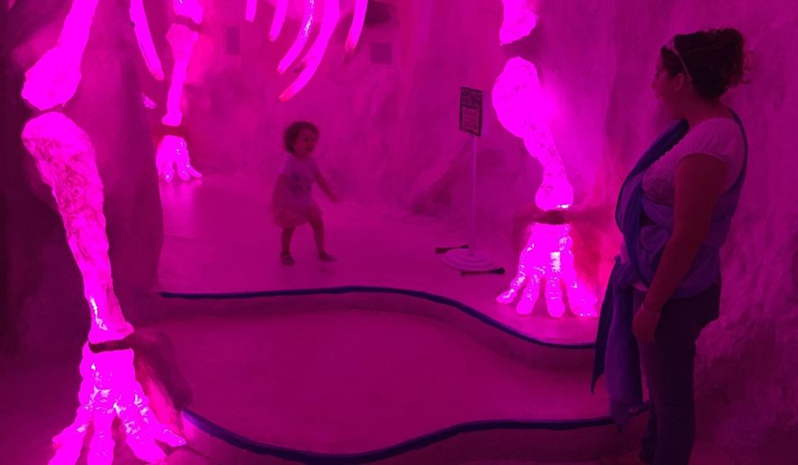 File - In this July 14, 2017, file photo, Caryn Saeger, 28, of Delta, Ohio, and her 2-year-old daughter Chloe explore Meow Wolf's mazelike exhibition space in Santa Fe, N.M. Creators of a popular immersive art entertainment project in Santa Fe, are expanding to a major metropolitan market with plans for an interactive exhibit and music venue on a wedge of highway-side property in an industrial stretch of downtown Denver. (AP Photo/Morgan Lee, File)