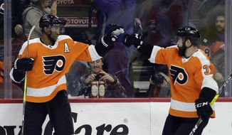 Philadelphia Flyers' Wayne Simmonds, left, and Radko Gudas celebrate after Simmonds' goal during the second period of an NHL hockey game against the New York Islanders, Thursday, Jan. 4, 2018, in Philadelphia. (AP Photo/Matt Slocum)