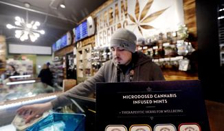 Cannabis consultant Juan Aguilar rings up a customer's marijuana purchase in the Herban Legends pot shop, Thursday, Jan. 4, 2018, in Seattle. Attorney General Jeff Sessions has rescinded an Obama-era policy that paved the way for legalized marijuana to flourish in states where the drug is legal across the country, creating new confusion about enforcement and use just three days after a new legalization law went into effect in California. (AP Photo/Elaine Thompson)