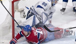 Montreal Canadiens right wing Brendan Gallagher (11) slides into Tampa Bay Lightning's goaltender Andrei Vasilevskiy during the third period of an NHL hockey game Thursday, Jan. 4, 2018, in Montreal. The Canadiens won, 2-1, in an overtime shootout. (Ryan Remiorz/The Canadian Press via AP)