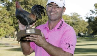 FILE - In this Oct. 29, 2017, file photo, Ryan Armour lifts the winner's trophy, a rooster named Reveille, after the Sanderson Farms Championship golf tournament in Jackson, Miss. Armour finally won at age 41, making him the oldest player in the winners-only field at the Sentry Tournament of Champions in Hawaii. (AP Photo/Rogelio V. Solis, File)