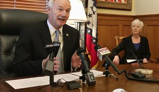 Arkansas Gov. Asa Hutchinson speaks to reporters at the state Capitol in Little Rock, Ark., on Thursday, Jan. 4, 2018, about a drop in the number of people enrolled in the state's Medicaid program. Hutchinson announced that the number of people on the traditional and expanded Medicaid programs dropped by more than 117,000 people from 2017 to 2018. (AP Photo/Andrew DeMillo)