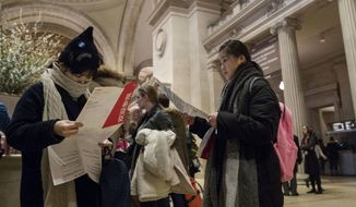 Visitors to the Metropolitan Museum of Art inspect the map of the museum after purchasing a ticket, Thursday, Jan. 4, 2018, in New York. Starting March 1, the museum will charge a mandatory $25 entrance fee to most adult visitors who don't live in New York state, the Met's president and CEO, Daniel Weiss, announced Thursday. Admission will still be pay-what-you-wish for New Yorkers. (AP Photo/Mary Altaffer)