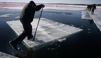 Bruce Nelson, left, and Mike Lint of the Wee Kut Ice Company harvest large chunks of ice that will be separated into blocks weighing over 550 pounds at Green Lake in Spicer, Minn. on Wednesday, Jan. 3, 2018. (Richard Tsong-Taatarii/Star Tribune via AP)