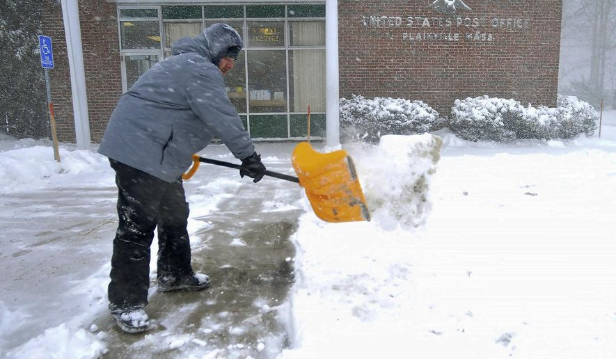 A pair of postal workers shovel the lot at the Plainville, Mass., Post Office Thursday, Jan. 4, 2018. The post office was open for business as usual.  (Mark Stockwell/The Sun Chronicle via AP)