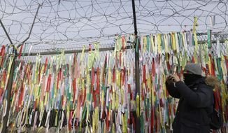 A visitor takes picture in front of ribbons wishing for the reunification of the two Koreas on the wire fence at the Imjingak Pavilion near the border village of Panmunjom, in Paju, South Korea, Thursday, Jan 4, 2018. North Korean leader Kim Jong Un reopened a key cross-border communication channel with South Korea for the first time in nearly two years Wednesday as the rivals explored the possibility of sitting down and talking after months of acrimony and fears of war. (AP Photo/Ahn Young-joon)