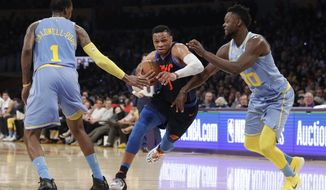 Oklahoma City Thunder's Russell Westbrook, center, is double-teamed by Los Angeles Lakers' Kentavious Caldwell-Pope, left, and Julius Randle during the first half of an NBA basketball game, Wednesday, Jan. 3, 2018, in Los Angeles. (AP Photo/Jae C. Hong)