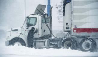 A truck driver works to remove his stuck truck along Delaware Route 1 in Rehoboth, Del., on Thursday, Jan. 4. 2018. A massive winter storm swept from the Carolinas to Maine. (Jason Minto/The Wilmington News-Journal via AP)
