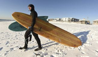 Kevin Cagle heads out to surf along Wrightsville Beach, N.C. Thursday Jan. 4, 2017. Just over 3 inches of snow covered the area after a winter storm moved through late last night. Areas along North Carolina's coast are reporting wind gusts of hurricane strength as part of a winter storm that's moving up the East Coast.  (Ken Blevins/The Wilmington News-Journal via AP)