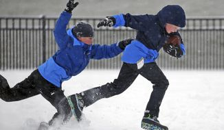 Nathan Cochran, 10, attempts to grab Jackson Robbins, 10, as they play football in the snow on Thursday, Jan. 4, 2018, in Newport News, Va. The National Weather Service issued a winter weather advisory for the upper part of the Peninsula and much of the Middle Peninsula. The advisory, issued around 1 p.m. Thursday, warns of snow, blowing snow and slippery roads until 6 p.m. (Aileen Devlin/The Daily Press via AP)