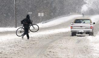 A cyclist gets a lift on Bypass Road during a snowstorm in Williamsburg, Va. Thursday, Jan. 4, 2018. (Alexa Welch Edlund /Richmond Times-Dispatch via AP)