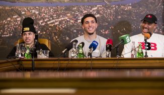 American basketball players LiAngelo Ball, center, and LaMelo Ball, left, and their father LaVar Ball participates in a media conference at the Harmony park hotel in Vaizgaikiemis village, Prienai district, Lithuania, Friday, Jan. 5, 2018. LiAngelo Ball and LaMelo Ball have both signed a one-year contracts to play for Lithuanian professional basketball club Prienai - Birstonas Vytautas in the southern Lithuania town of Prienai, some 110 km (68 miles) from the Lithuanian capital Vilnius.(AP Photo/Mindaugas Kulbis)