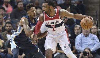 Washington Wizards guard John Wall (2) controls the ball against Memphis Grizzlies guard Mario Chalmers during the first half of an NBA basketball game Friday, Jan. 5, 2018, in Memphis, Tenn. (AP Photo/Brandon Dill)
