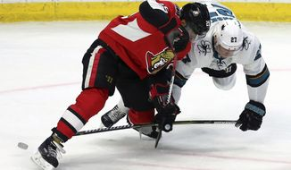 Ottawa Senators' Johnny Oduya (29) and San Jose Sharks' Joonas Donskoi (27) fight for the puck during second-period NHL hockey game action in Ottawa, Friday, Jan. 5, 2018. (Fred Chartrand/The Canadian Press via AP)