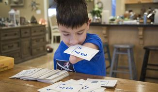 In a Dec. 11, 2017 photo, Bowen Toomey, 9, runs through his multiplication flash cards at home in Eagle, Idaho. Bowen was born in 2008 without arms or legs, given up by his birth mother in Serbia and placed in a government-run orphanage. He was adopted by an Eagle, Idaho, family in 2010 and has inspired people in the community and around the world. (Katherine Jones/Idaho Statesman via AP)