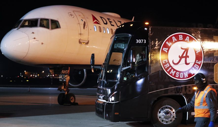 A bus carrying the Alabama football team begins to leave Hartsfield-Jackson Atlanta International Airport after the team arrived Friday, Jan. 5, 2018, in Atlanta for Monday night's NCAA college football championship game against Georgia (AP Photo/John Bazemore)