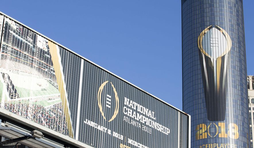 The Atlanta Westin hotel is decorated an image of the College Football Playoff National Championship Trophy, Friday, Jan. 5, 2018, in Atlanta. Georgia is to take on Alabama on Monday. (Alyssa Pointer/Atlanta Journal-Constitution via AP)