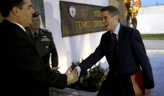Cyprus' Defense Minister Christoforos Fokaides, left, welcomes the Britain's Defence Secretary Gavin Williamson at the Defense Ministry for their talks in capital NIcosia, Cyprus, Friday, Jan. 5, 2018. Williamson says authorities are looking to ensure British armed forces 'work closer and more supportively' with Cyprus' armed forces in tackling common challenges. (AP Photo/Petros Karadjias)