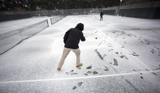 Vincent Sottile, center, and his brother Mike Sottile play hockey on the public tennis courts at Forsyth Park, Wednesday, Jan. 3, 2018, in Savannah, Ga. A brutal winter storm scattered a wintry mix of snow, sleet and freezing rain from normally balmy Florida up the Southeast seaboard Wednesday. (AP Photo/Stephen B. Morton)