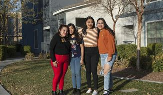 In this Friday, Dec. 22, 2017 photo, Ericka Lopez, from left, and her daughters Emily Garcia, 12, Anna Ramos Lopez, 16, and Glenda Ramos Lopez, 20,stand in front of their home in Las Vegas. Lopez fears her family will be split in half in future immigration decisions. Some are citizens and some are under temporary protected status.  (Rachel Aston/Las Vegas Review-Journal via AP)