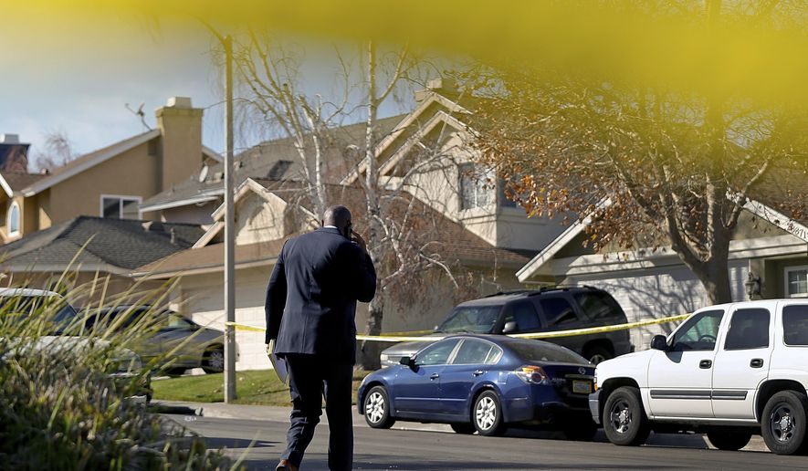 Los Angeles County Sheriff's Department Lt. Rodney Moore walks towards a police-taped home where four people have been found shot to death in Santa Clarita, Calif., Friday, Jan. 5, 2018. Authorities believe a man shot and killed his wife and two children before turning the gun on himself in their Southern California home, where their bodies were found Friday. (AP Photo/Damian Dovarganes)