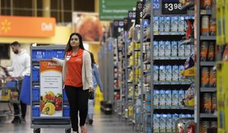 ADVANCE FOR MONDAY, JAN. 8, 2018, AND THEREAFTER - In this Thursday, Nov. 9, 2017, photo, Laila Ummelaila, a personal shopper at the Walmart store in Old Bridge, N.J., pulls a cart with bins as she shops for online shoppers. Personal shoppers collect items on online orders and greet customers at a pickup location in the parking lot. (AP Photo/Julio Cortez)