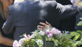 FILE - In this June 29, 2006, file photo, John Ramsey hugs his son, Burke, facing camera, at the graves of his wife, Patsy, and daughter JonBenet, during services for his wife at the St. James Episcopal Cemetery in Marietta, Ga. A judge has declined to dismiss a $750 million defamation lawsuit filed against CBS by JonBenet Ramsey's brother, Burke Ramsey. The Boulder Daily Camera reports a circuit court judge in Michigan on Friday, Jan. 5, 2018, denied a motion by CBS and other defendants who asked that he toss the case. (AP Photo/Ric Feld, File)