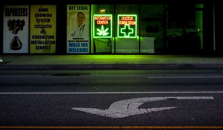 FILE - In this June 12, 2010, file photo, a medical marijuana dispensary leaves its lights on after hours on in Los Angeles. California is pulling ads aimed at discouraging stoned driving after critics said it promoted marijuana use. The ad campaign was rolled out as California began allowing licensed stores to sell pot to adults on Jan. 1, 2018. (AP Photo/Adam Lau, File)