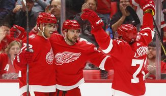 Detroit Red Wings' Tomas Tatar, center, celebrates his goal against the Florida Panthers with Andreas Athanasiou, left, and Dylan Larkin, right, in the second period of an NHL hockey game Friday, Jan. 5, 2018, in Detroit. (AP Photo/Paul Sancya)