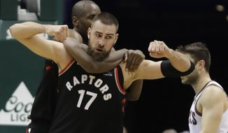 Toronto Raptors' Jonas Valanciunas celebrates with Serge Ibaka after making a basket and being fouled during the second half of an NBA basketball game against the Milwaukee Bucks Friday, Jan. 5, 2018, in Milwaukee. (AP Photo/Morry Gash)