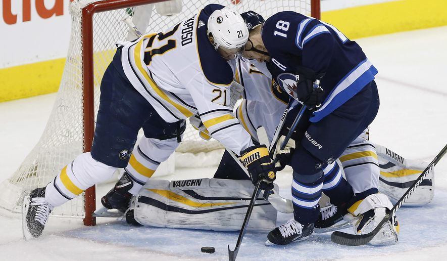 Winnipeg Jets' Bryan Little (18) and Buffalo Sabres' Kyle Okposo (21) scramble for the puck in front of Sabres goaltender Chad Johnson (31) during the first period of an NHL hockey game Friday, Jan. 5, 2018, in Winnipeg, Manitoba. (John Woods/The Canadian Press via AP)