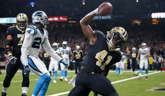 FILE - In this Dec. 3, 2017, file photo, New Orleans Saints running back Alvin Kamara (41) celebrates his touchdown in front of Carolina Panthers cornerback James Bradberry (24) during the first half of an NFL football game in New Orleans. Whether Saints running backs Mark Ingram and Kamara are standing side-by-side in the Superdome locker room for one of their joint postgame news conferences, or side-by-side on the sidelined of a college football game they attended together, it looks as though they not only feel invested in one another's success, but actually like one another. (AP Photo/Butch Dill, File)