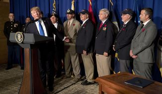 President Donald Trump is flanked by veterans at an event to sign a proclamation honoring veterans at the Hyatt Regency Danang Resort in Danang, Vietnam, on Nov. 10, 2017. (Associated Press) **FILE**