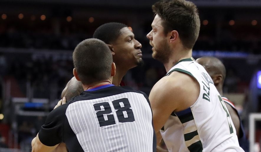 Washington Wizards guard Bradley Beal, center, and Milwaukee Bucks guard Matthew Dellavedova, right, are separated by referee Kevin Scott during the second half of an NBA basketball game Saturday, Jan. 6, 2018, in Washington. Dellavedova was ejected after the play. The Bucks won 110-103. (AP Photo/Alex Brandon)