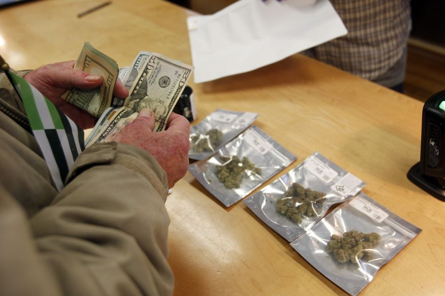 In this Monday, Jan. 1, 2018 file photo, a customer purchases marijuana at the Harborside marijuana dispensary in Oakland, Calif., on the first day that recreational marijuana was sold legally in California. (AP Photo/Mathew Sumner)