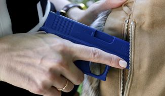 In this Aug. 29, 2016 file photo, Marilyn Smolenski uses a mock gun to demonstrate how to pull a handgun out of concealed carry clothing she designs at her home in Park Ridge, Ill. On Feb. 22, 2018, the New Hampshire House of Representatives voted down a bill that allows concealed-carry of firearms on state university campuses. (AP Photo/Tae-Gyun Kim) **FILE**