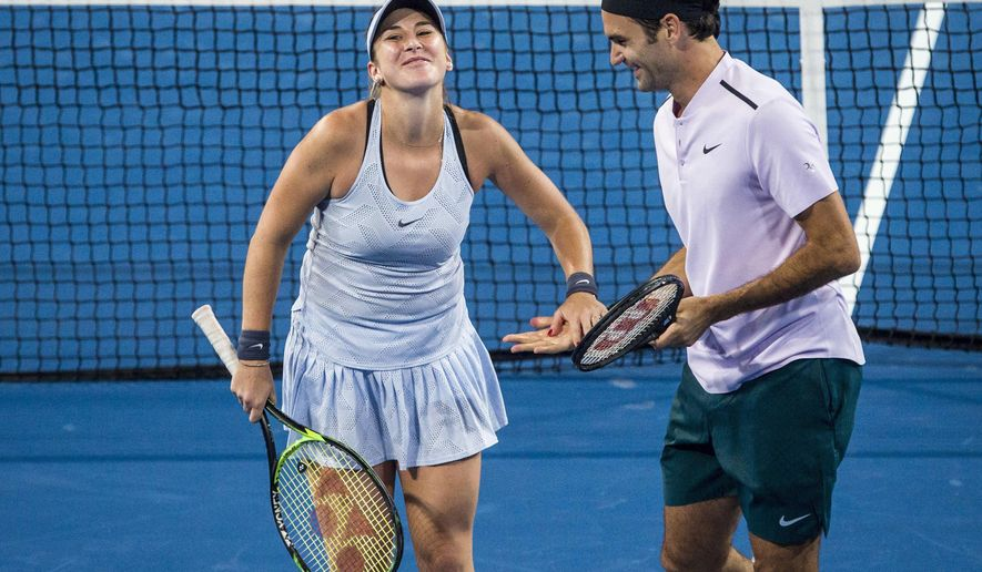 FILE - This is a  Tuesday, Jan. 2, 2018 file photo of Belinda Bencic, left, and Roger Federer of Switzerland as they clap hands during their mixed doubles match against Karen Khachanov and Anastasia Pavlyuchenkova of Russia at the Hopman Cup tennis tournament in Perth, Australia.  Roger Federer and Belinda Bencic advanced Switzerland into the Hopman Cup final with straight-set singles victories over their American opponents. (Tony McDonough/AAP Image, File via AP)