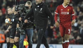 Liverpool manager Juergen Klopp, left, celebrates with winning goal scorer Liverpool's Virgil van Dijk, right, after the final whistle during the English FA Cup Third Round soccer match between Liverpool and Everton at Anfield in Liverpool, England, Friday, Jan. 5, 2018. (AP Photo/Rui Vieira)