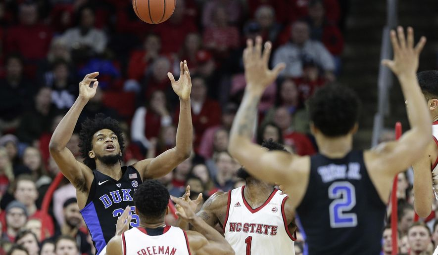 Duke's Marvin Bagley III, left, reaches for the ball in front of North Carolina State's Allerik Freeman (12) and Lennard Freeman (1) during the first half of an NCAA college basketball game in Raleigh, N.C., Saturday, Jan. 6, 2018. (AP Photo/Gerry Broome)